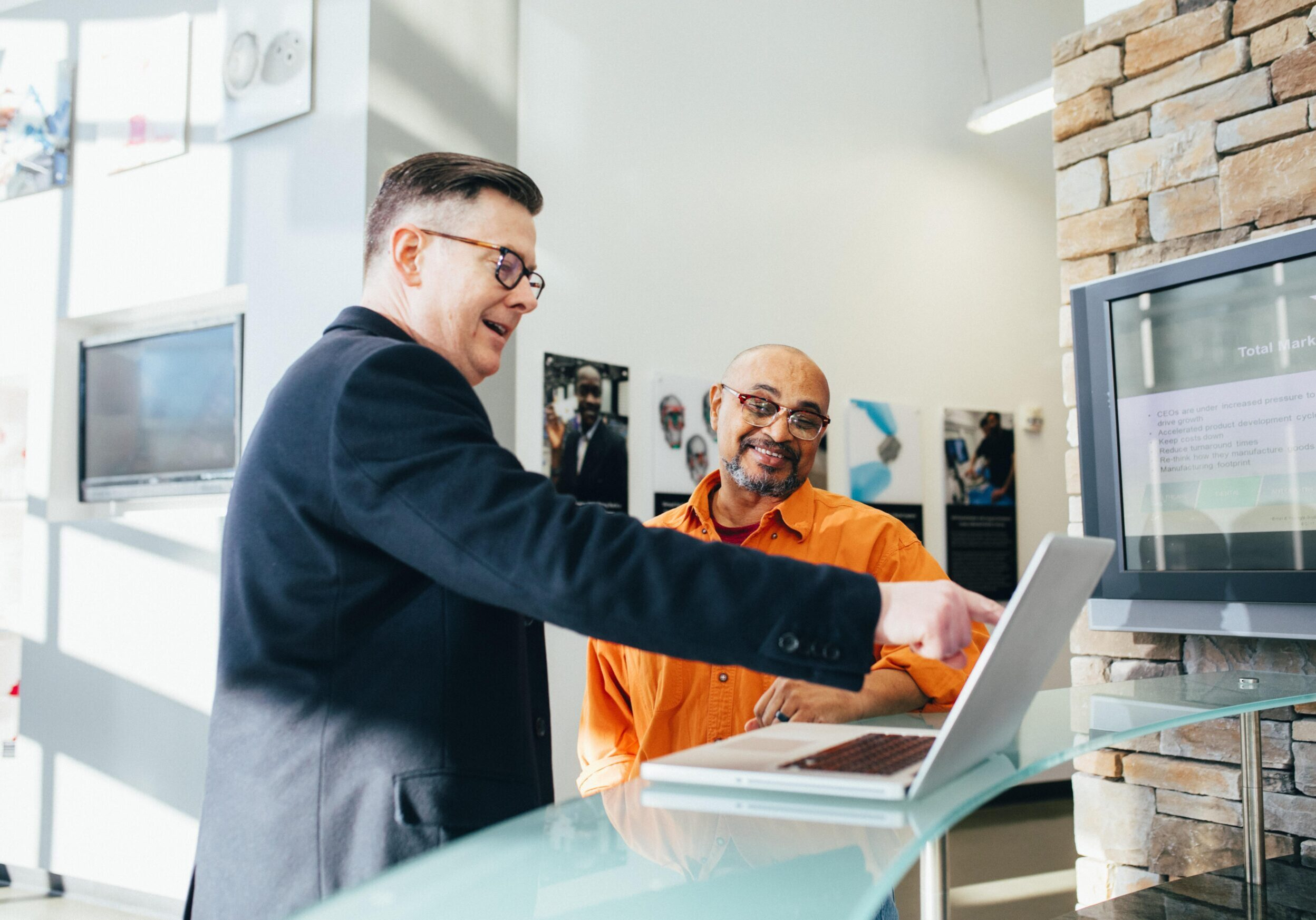 Two mentors meeting and pointing to a laptop